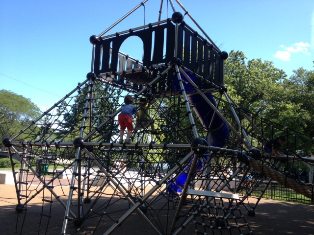 A massive rope play structure challenges kids to climb high