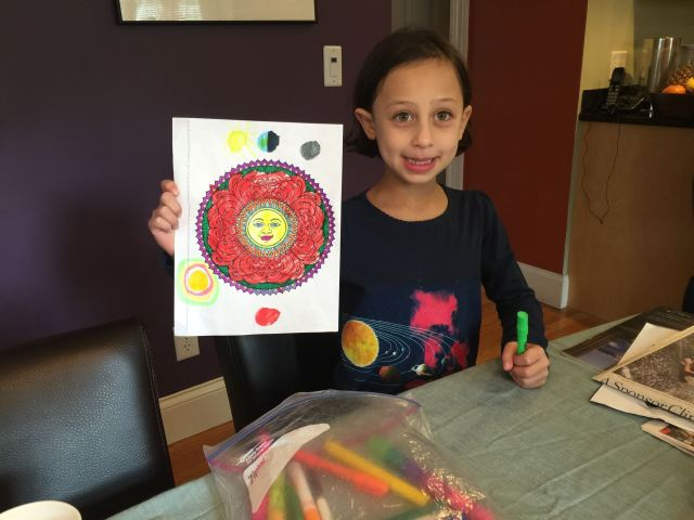 Ayelet wearing her space t-shirt, part way through drawing her solar system picture.