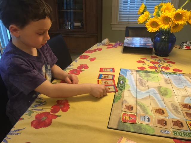 The child lays out a series of cards to move forward and turn right or left to guide the turtle to the goal.